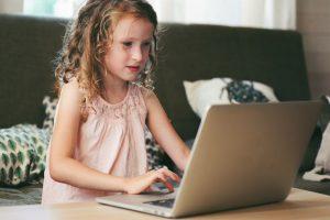 Jeune fille qui suit un cours en ligne avec un ordinateur.